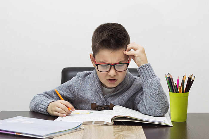 young boy frustrated over homework, writing at home. Boy studying at table. Kid drawing with a pencil.
